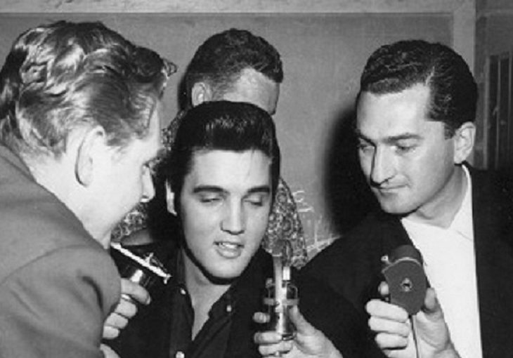 Marke Raines, right, holds a CKNW microphone as Elvis Presley speaks backstage in Vancouver on Aug. 31, 1957.