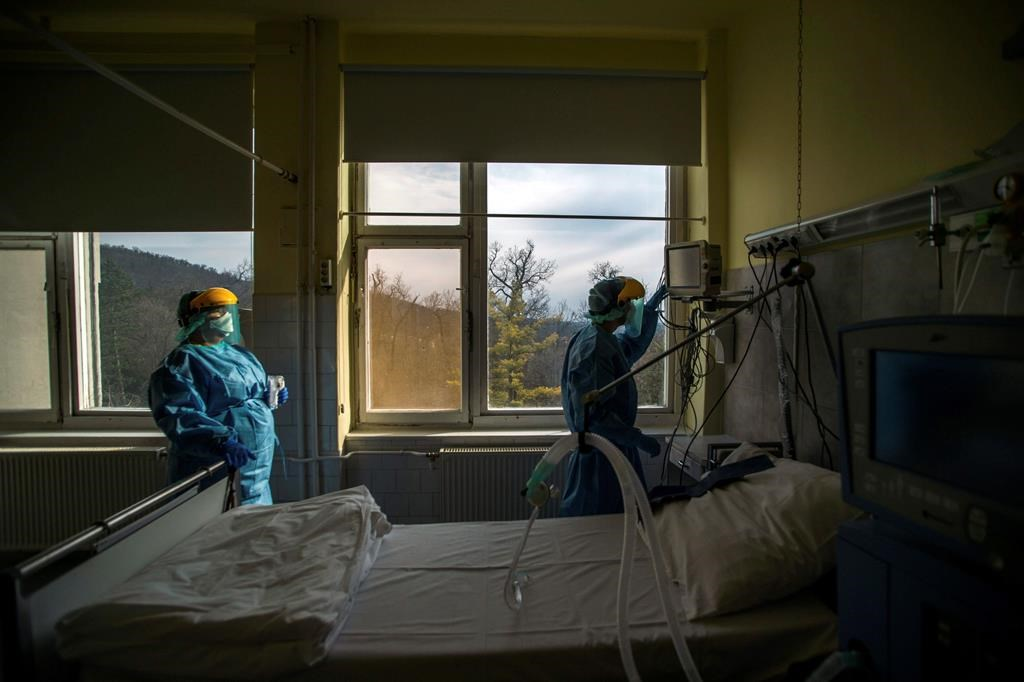 FILE - In this March 24, 2020, file photo, medical staff members check a ventilator in protective suits at the care unit for the new COVID-19 infected patients inside the Koranyi National Institute of Pulmonology in Budapest.