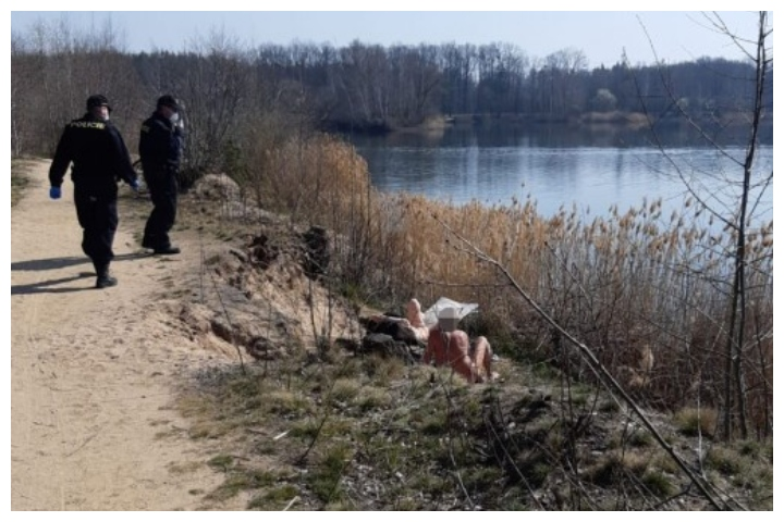 Police interrupt two sunbathers near a pond in the Czech Republic on March 27, 2020.