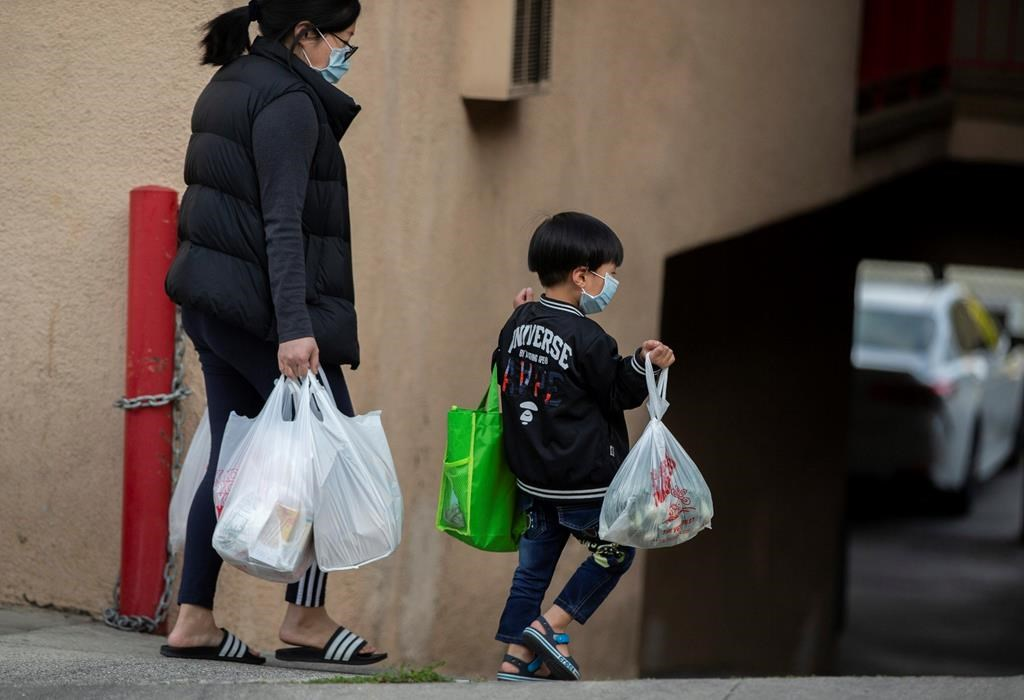In this April 2, 2020 file photo, an adult and a child, both wearing face masks amid the coronavirus outbreak, carry bags in the Chinatown neighborhood of Los Angeles.