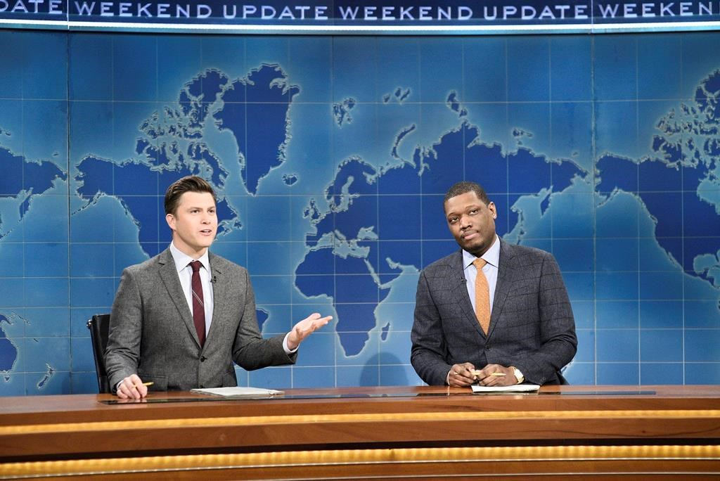 """This Feb. 29, 2020 photo released by NBC shows Colin Jost, left, and Michael Che during the Weekend Update sketch on """"Saturday Night Live"""" in New York. The show will be back on the air this weekend with a show that abides by social distancing rules. NBC says the comedy sketch show will include include a """"Weekend Update"""" news segment and original content from """"SNL"""" cast members. The material will be produced remotely, in compliance with efforts to limit the spread of the coronavirus. (Will Heath/NBC via AP)."""
