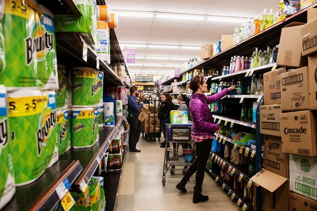 In this March 12, 2020, file photo, customers shop for cleaning products as market employees restock shelves.