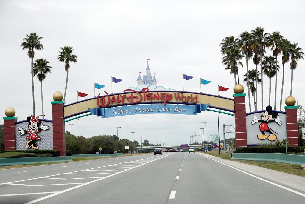 In this March 16, 2020, file photo, the road to the entrance of Walt Disney World has few cars, in Lake Buena Vista, Fla.