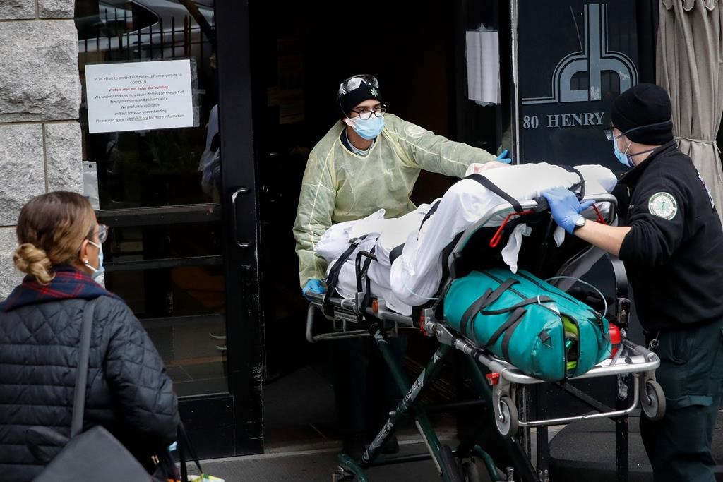 FILE- In this April 17, 2020, file photo, a patient is wheeled into Cobble Hill Health Center by emergency medical workers in the Brooklyn borough of New York.