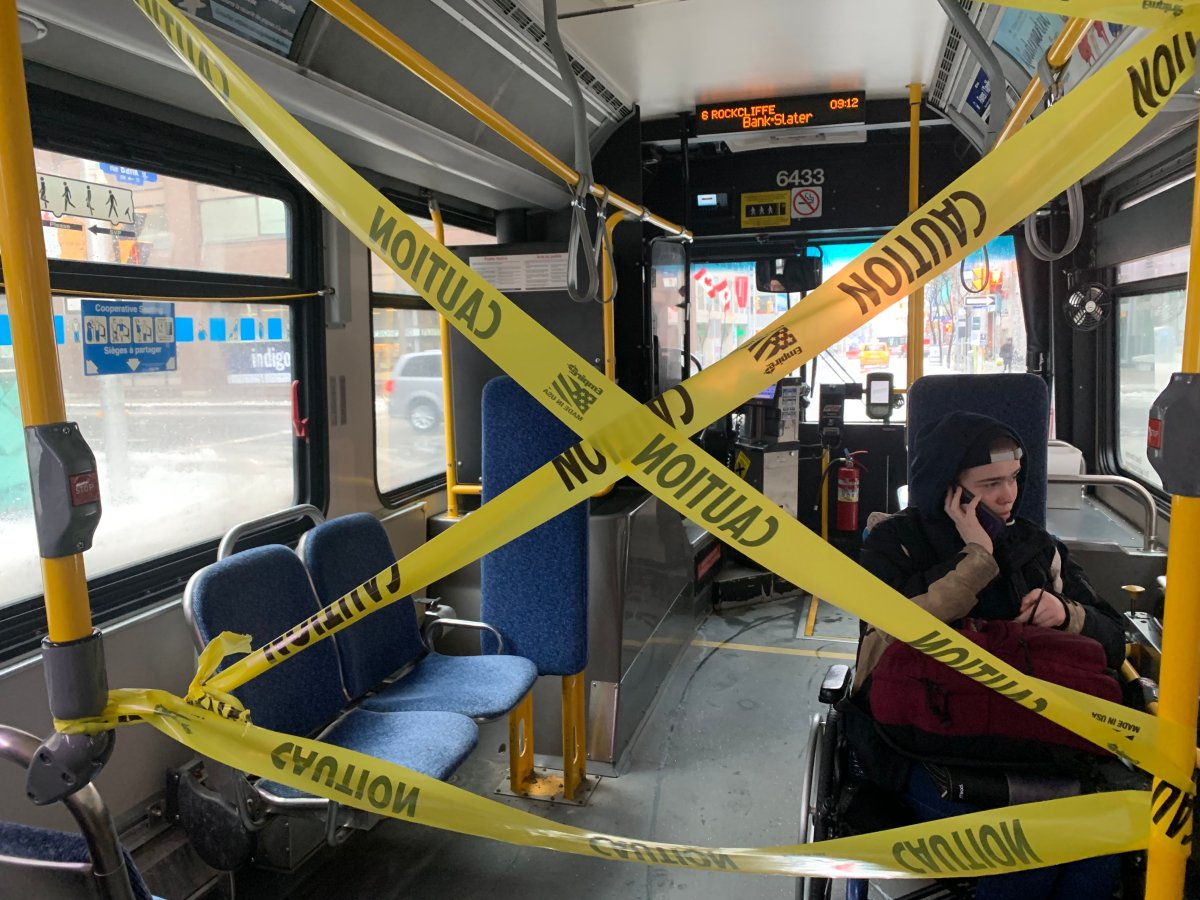 Yellow caution tape separates the driver's cab and the accessible seating area on an OC Transpo bus from the rear area of the vehicle. The transit agency will remove the tape but ask riders to wear masks when service is gradually restored starting in June.