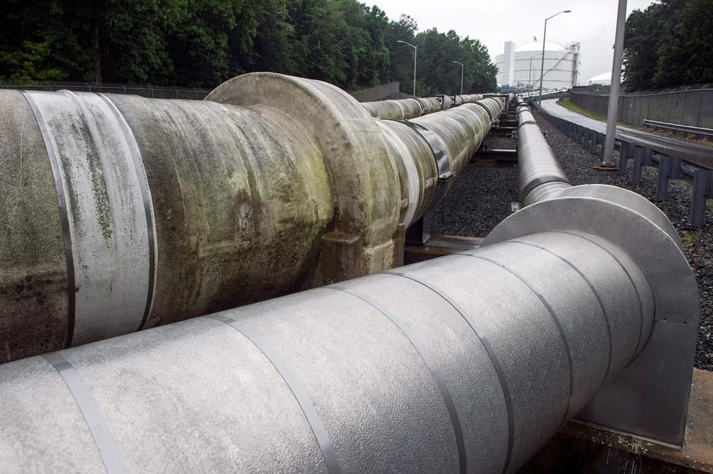 In this June 12, 2014, photo, pipes carrying liquified natural gas to and from a holding tank, seen in background, at Dominion Energy's Cove Point LNG Terminal in Lusby, Md. THE CANADIAN PRESS/AP/Cliff Owen.