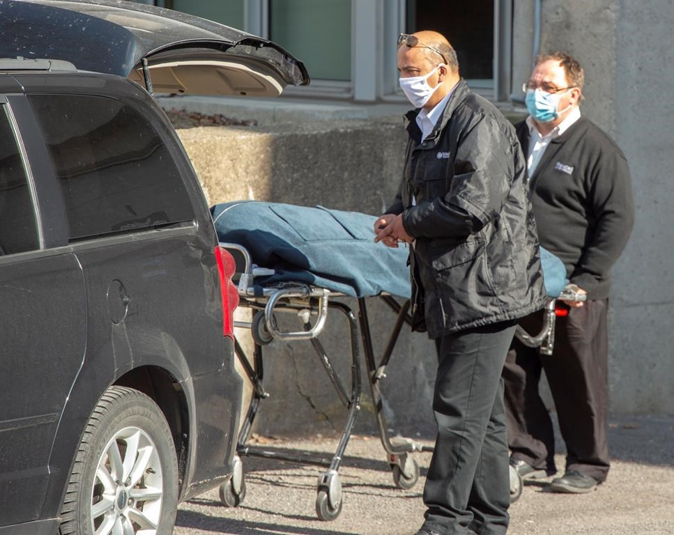 Funeral home workers remove a body from the Centre d'hebergement Sainte-Dorothee Friday April 17, 2020 in Laval Que.