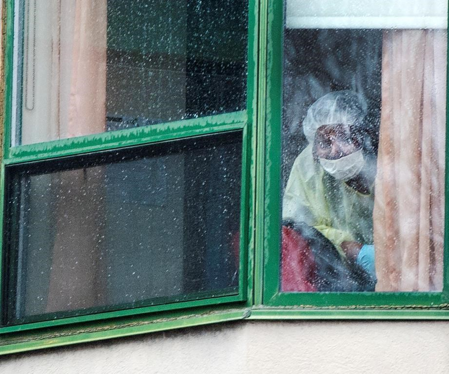 A person wearing protective equipment looks out of a window at the Herron seniors residence Monday April 13, 2020 in Dorval near Montreal's Trudeau airport. Thirty-one residents are confirmed to have died in the past month.