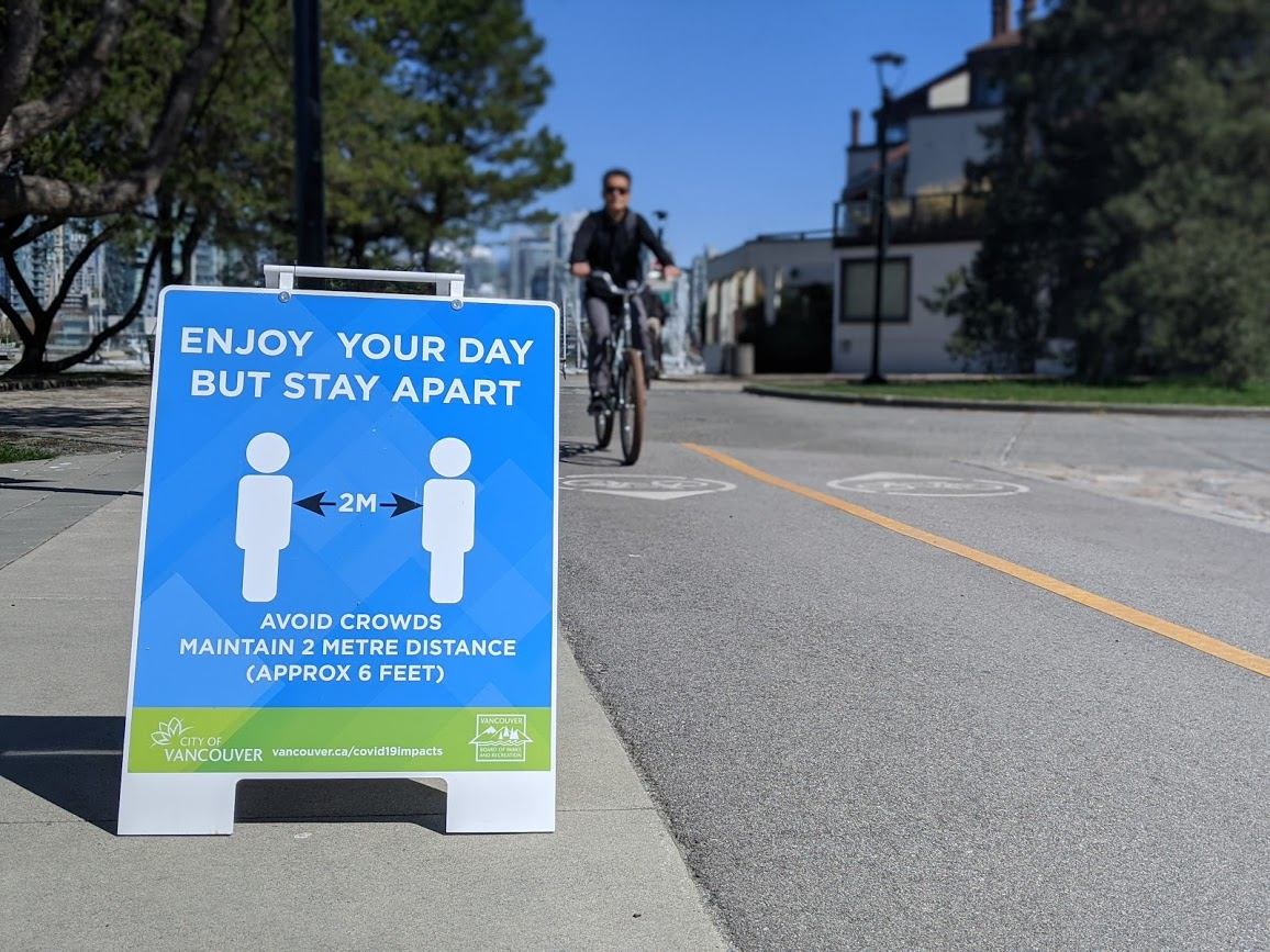 Signs on Vancouver's seawall ask pedestrians and cyclists to stay two metres apart during the COVID-19 pandemic.