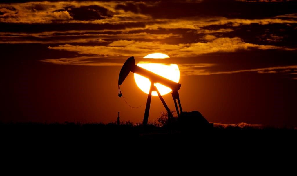 The sun sets behind an idle pump jack.