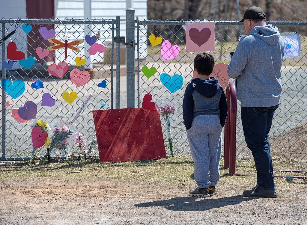 A man and his son pay repects at a memorial to Lisa McCully, a teacher at Debert Elementary School in Debert, N.S. on Tuesday, April 21, 2020.