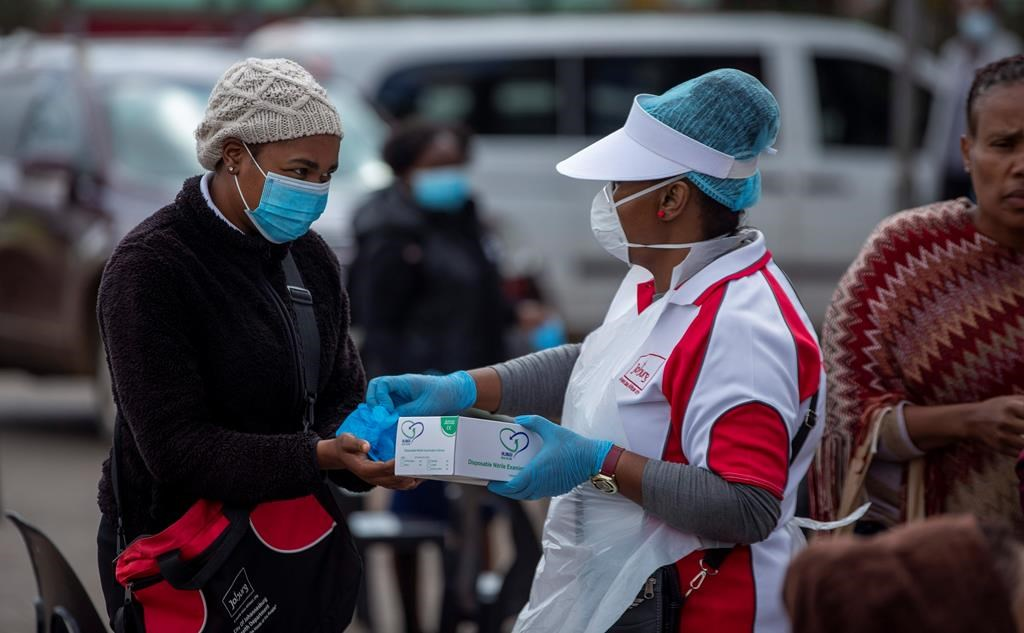 A health worker hands over surgical gloves to a woman, whilst queuing to undergo screening and testing for COVID-19, in Lenasia, south of Johannesburg, South Africa, Wednesday, April 8, 2020. South Africa and more than half of Africa's 54 countries have imposed lockdowns, curfews, travel bans or other restrictions to try to contain the spread of COVID-19. The new coronavirus causes mild or moderate symptoms for most people, but for some, especially older adults and people with existing health problems, it can cause more severe illness or death. (AP Photo/Themba Hadebe).