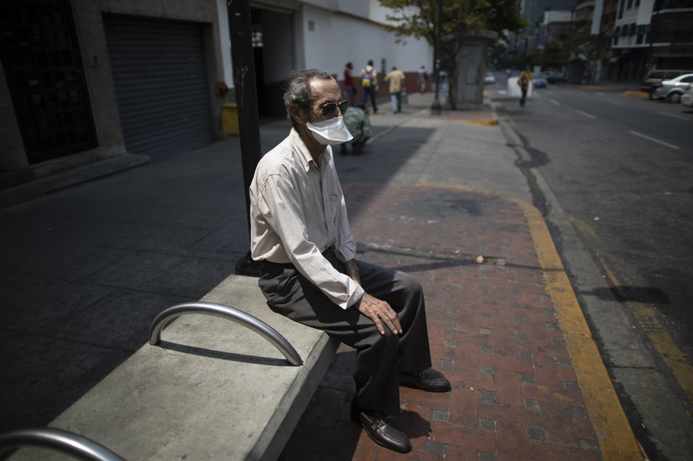 An elderly man wearing a mask to avoid the spread of the new coronavirus suns himself on a bench in Caracas, Venezuela, Sunday, May 24, 2020.