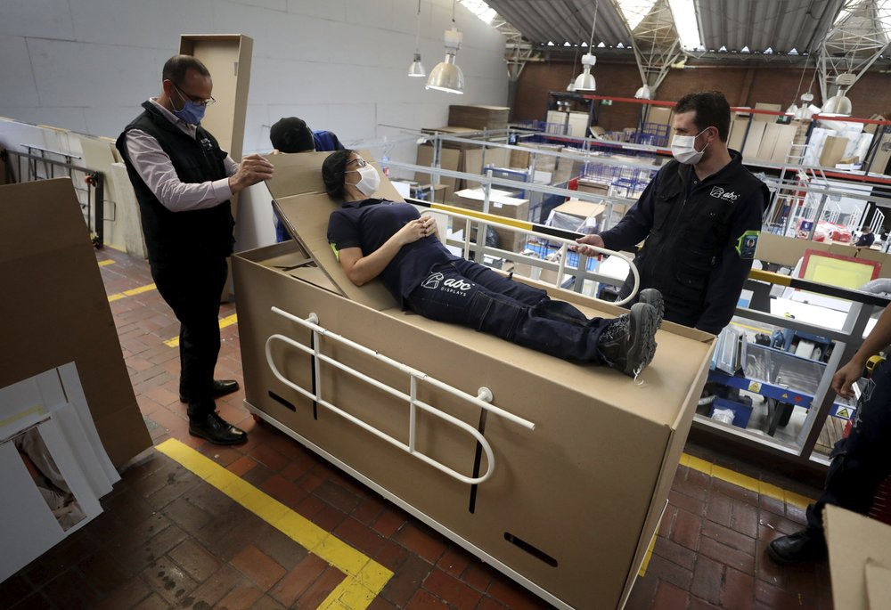 Rodolfo Gomez, left, and his employees demonstrate how their design of a cardboard box can serve as both a hospital bed and a coffin, designed for COVID-19 patients, in Bogota, Colombia, Friday, May 8, 2020. Gomez said he plans to donate the first units to Colombia's Amazonas state, and that he will sell others to small hospitals for 87 dollars.