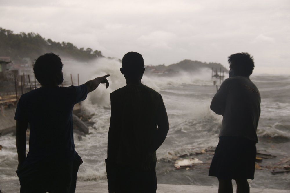 Men watch as strong waves caused by typhoon Vongfong batter the coastline of Catbalogan city, Western Samar province, eastern Philippines, Thursday, May, 14, 2020. A strong typhoon slammed into the eastern Philippines on Thursday after authorities evacuated tens of thousands of people while trying to avoid the virus risks of overcrowding emergency shelters.