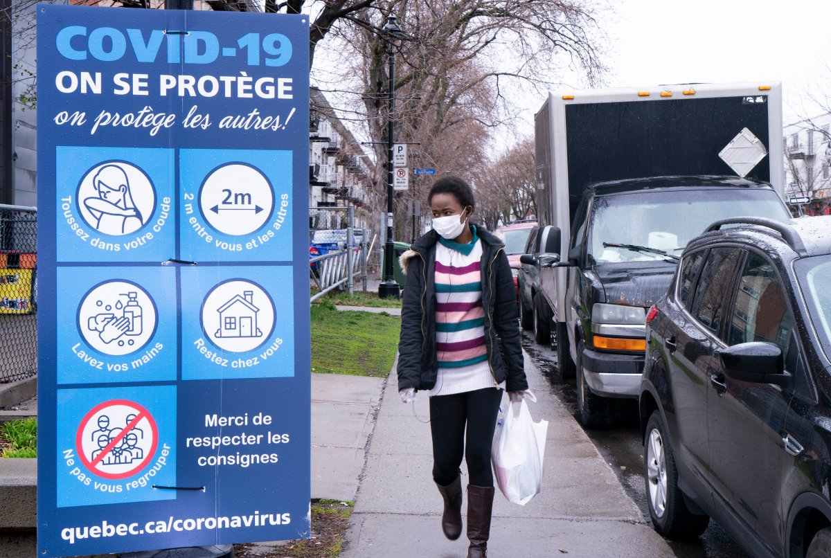 A woman walks past a COVID-19 sign in Montreal North.