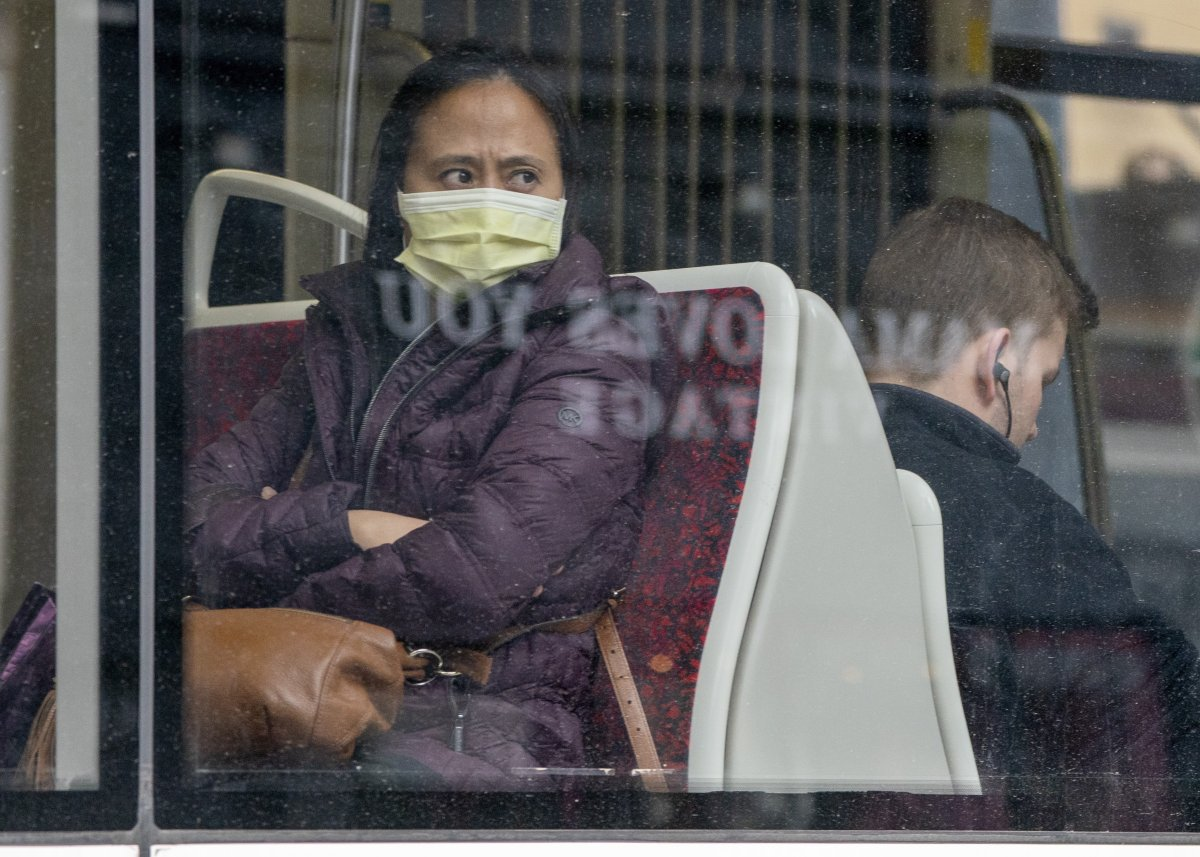 A woman wears a mask as she rides a TTC streetcar in Toronto on Friday, March 20, 2020.
