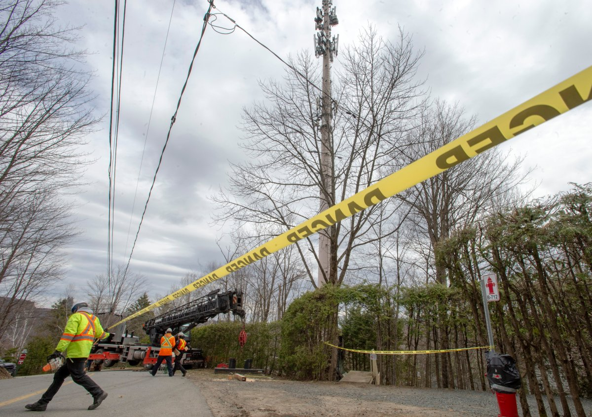 Technicians repair a cell tower after a fire that police are calling suspicious Monday May 4, 2020 in Piedmont, Que. There have been fires at two other cell towers in the area in the past few days.