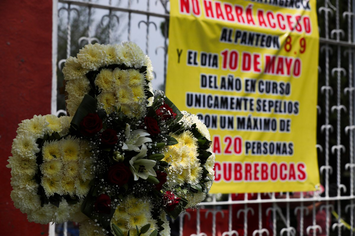 """A funeral wreath is displayed at the entrance of the San Isidro cemetery near a sign that reads in Spanish: """"There will be no access to the cemetery on May 8, 9 and 10"""" in Mexico City, Friday, May 8, 2020."""