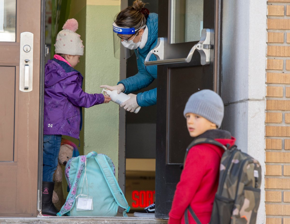 FILE: Students get their hands sanitized as they enter Ecole Marie Rose as elementary schools outside the greater Montreal area reopen.