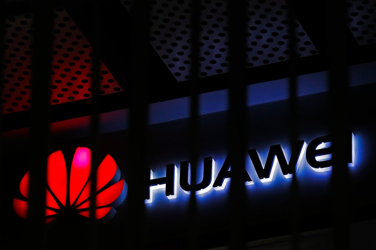 FILE - In this March 8, 2019, file photo, A logo of Huawei retail shop is seen through a handrail inside a commercial office building in Beijing.