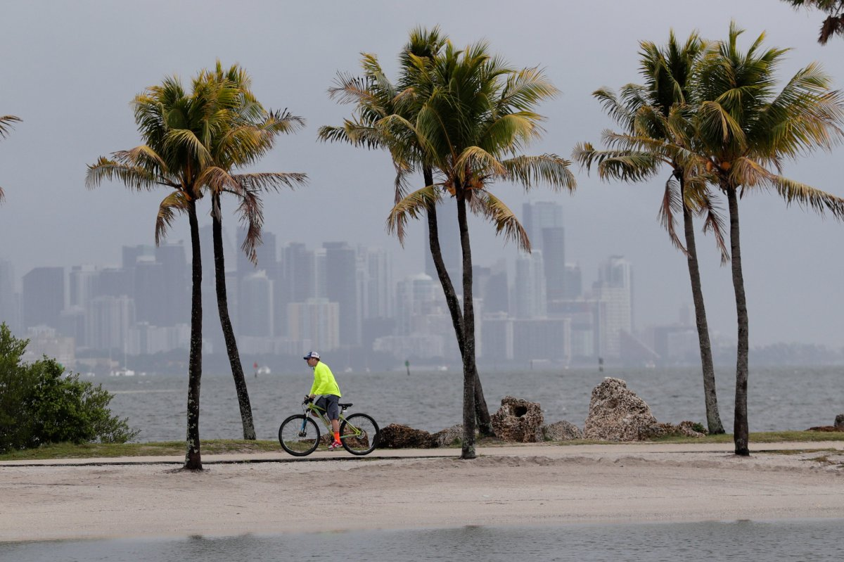 The Miami skyline is shrouded in clouds as a cyclist rides along Biscayne Bay at Matheson Hammock Park, Friday, May 15, 2020.