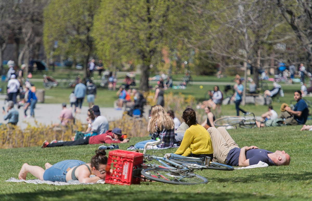 People gather in a city park on a warm sunny day in Montreal, Monday, May 18, 2020, as the COVID-19 pandemic continues in Canada and around the world.