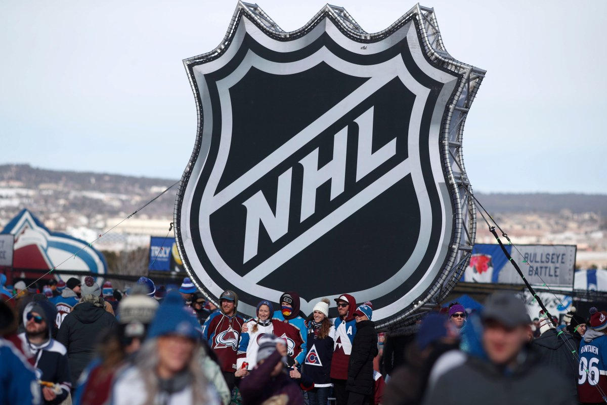 In this Saturday, Feb. 15, 2020, file photo, fans pose below the NHL league logo at a display outside Falcon Stadium before an NHL Stadium Series outdoor hockey game between the Los Angeles Kings and Colorado Avalanche, at Air Force Academy, Colo.
