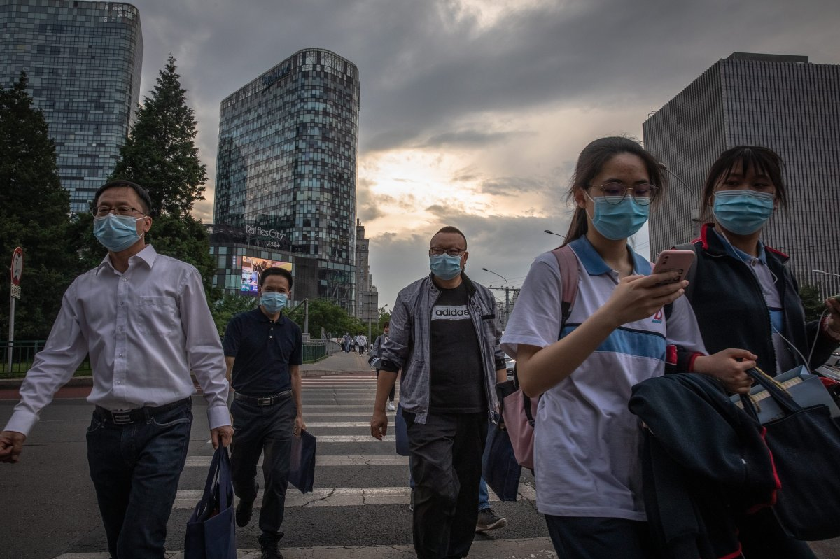 People wearing protective face masks cross a road during evening rush-hour on the first day of China's National People's Congress (NPC) in Beijing, China, 22 May 2020.