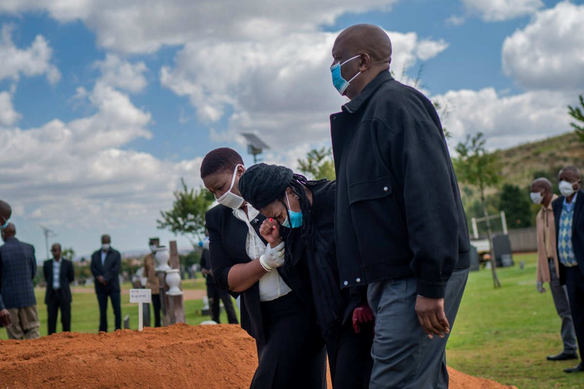FILE - In this Sunday, April 12, 2020 file photo, relatives grieve for Benedict Somi Vilakasi, a Soweto coffee shop manager who died of a COVID-19 infection in a Johannesburg hospital, at his burial ceremony at the Nasrec Memorial Park outside Johannesburg, South Africa Thursday, April 16, 2020.