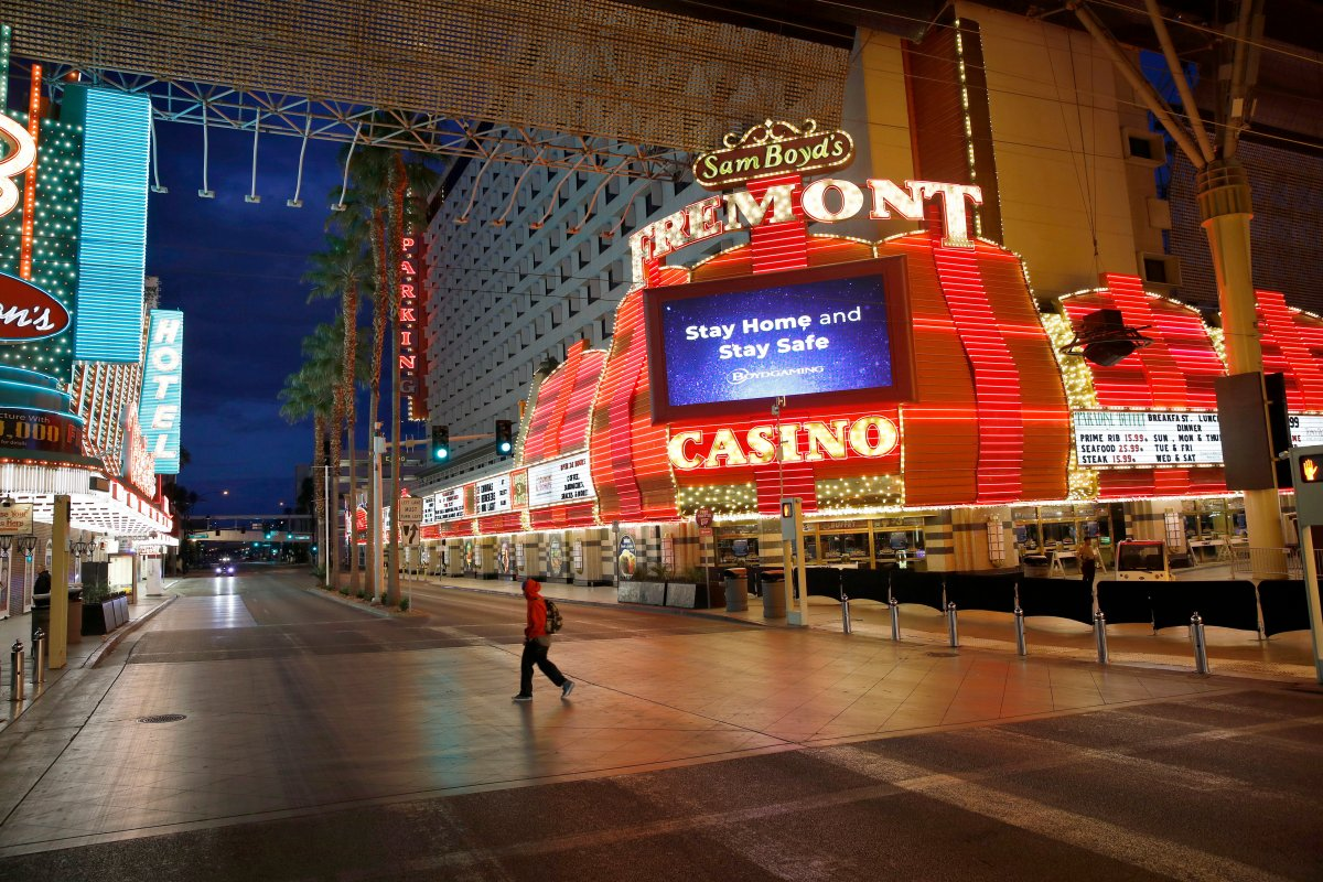 FILE - In this March 21, 2020, file photo, a man walks along a usually busy Fremont Street after casinos were ordered to shut down due to the coronavirus outbreak in Las Vegas.