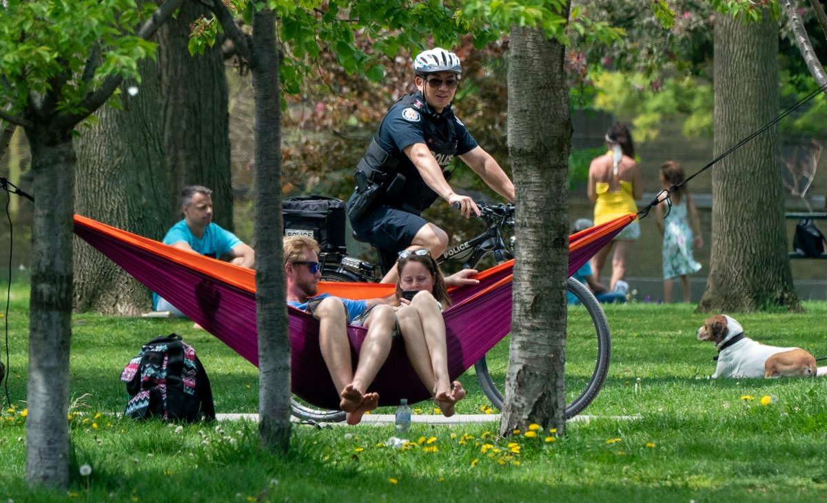 A bicycle police officer patrols Trinity Bellwoods Park in Toronto on Sunday, May 24, 2020. Warm weather and a reduction in COVID-19 restrictions has many looking to the outdoors for relief. THE CANADIAN PRESS/Frank Gunn.