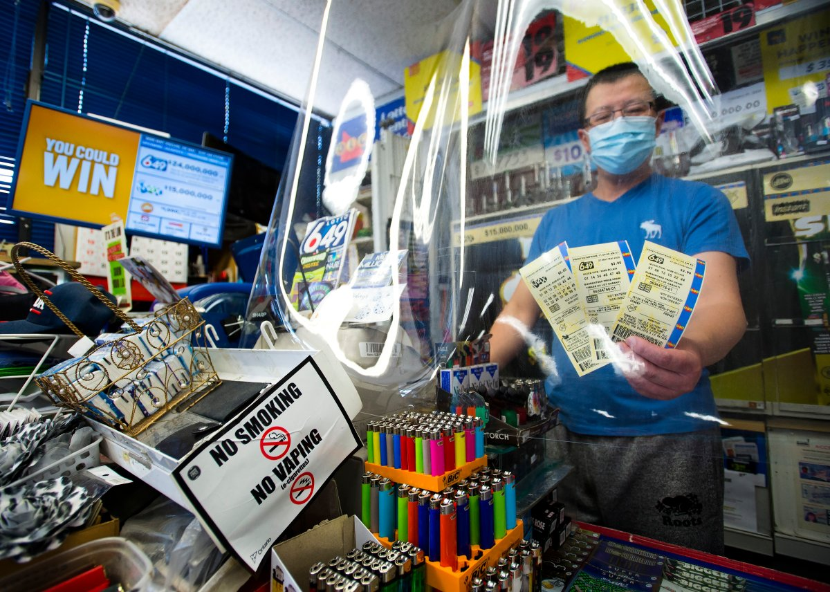 A convince store owner hands OLG 649 and Lotto Max tickets at his store during the COVID-19 pandemic in Mississauga, Ont., on Monday, May 25, 2020. Premier Doug Ford's government gives $500M loan to Ontario Lottery and Gaming.