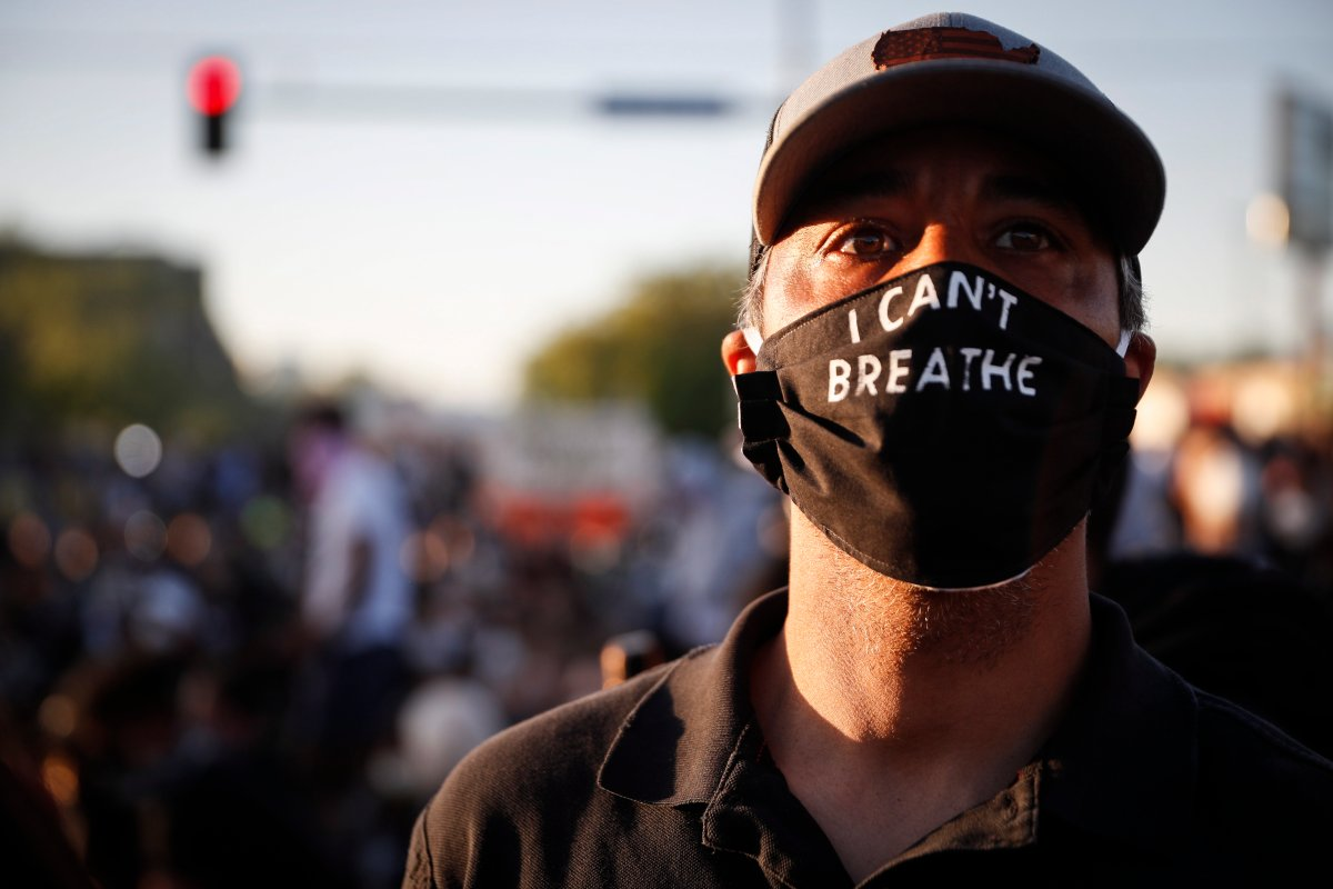 """A man attends a protest outside the Minneapolis 5th Police Precinct while wearing a protective mask that reads """"I CAN'T BREATHE"""", Saturday, May 30, 2020, in Minneapolis."""