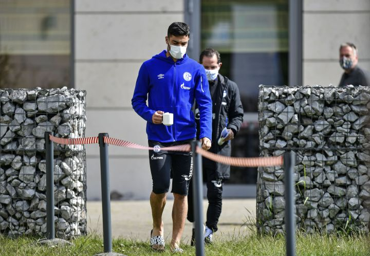 Schalke defender Ozan Kabak leaves the hotel, where his team stays in quarantine, with a face mask in Gelsenkirchen, Germany, Thursday, May 14, 2020. Bundesliga will now restart on May 16, 2020 when Borussia Dortmund will play the derby against FC Schalke 04 at home without spectators due to the coronavirus outbreak.