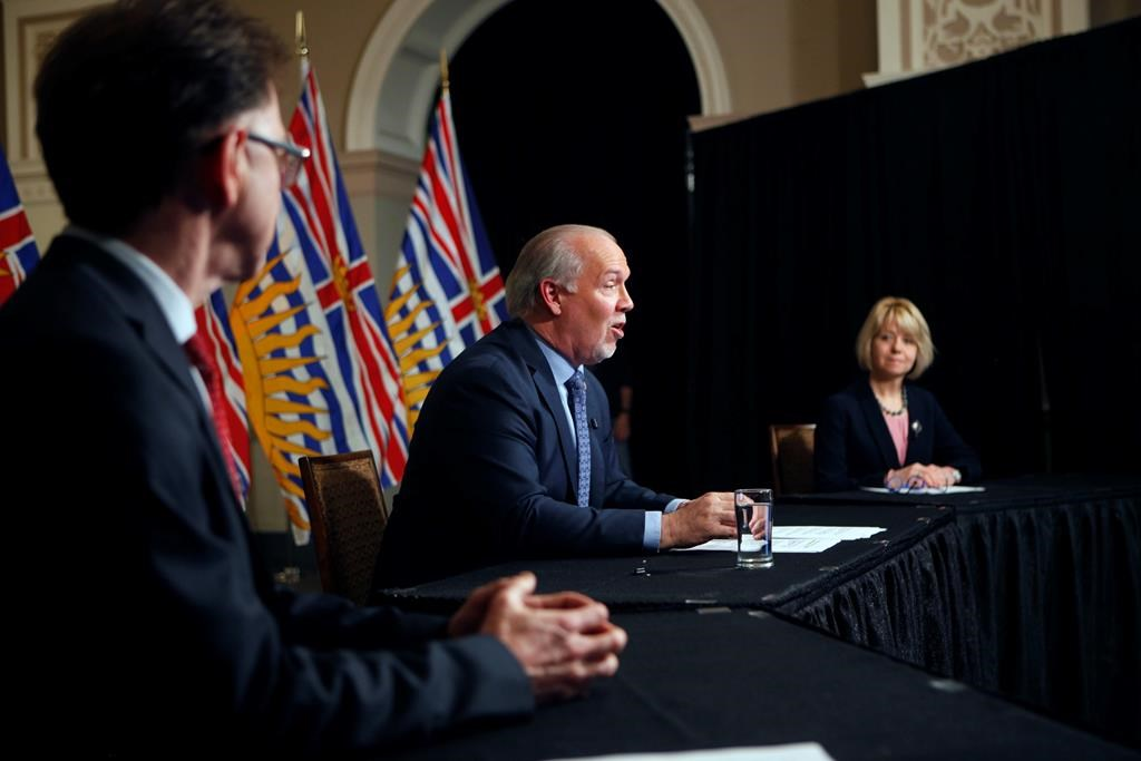 Premier John Horgan is joined by Provincial Health Officer Dr. Bonnie Henry and Health Minister Adrian Dix as they discuss reopening the province's economy in phases in response to the COVID-19 pandemic during a press conference in the rotunda at Legislature in Victoria, B.C., on Wednesday May 6, 2020.