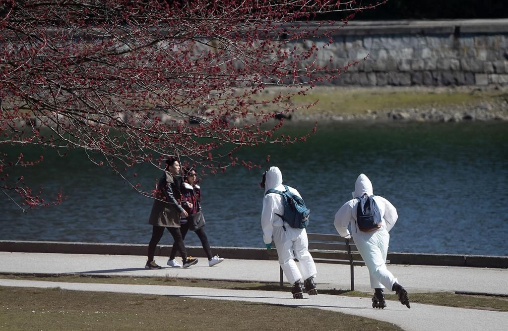 Two people wearing personal protective equipment, including respirators and coverall suits in-line skate on the seawall at Stanley Park in Vancouver on Sunday, April 5, 2020.