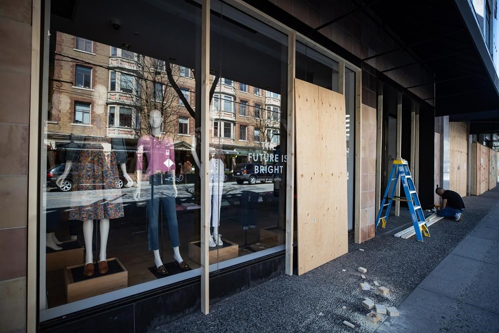 A worker boards up a closed clothing store in Vancouver, on Thursday, April 16, 2020.
