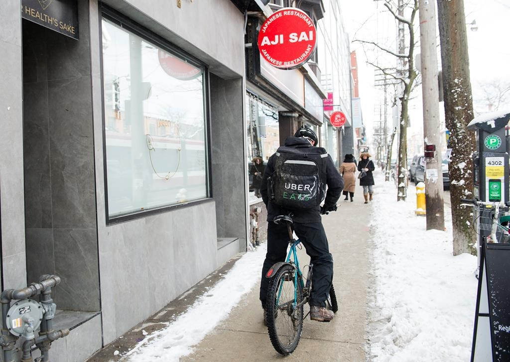An Uber Eats courier is pictured as they pick up an order for delivery from a restaurant in Toronto, Thursday, Feb. 27, 2020.