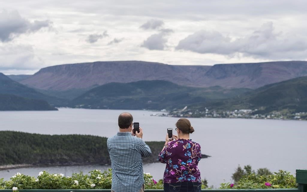 Tourists take pictures with their mobile phones of the Gulf of St. Lawrence in Gros Morne National Park, Newfoundland and Labrador, on Monday, August 15, 2016.