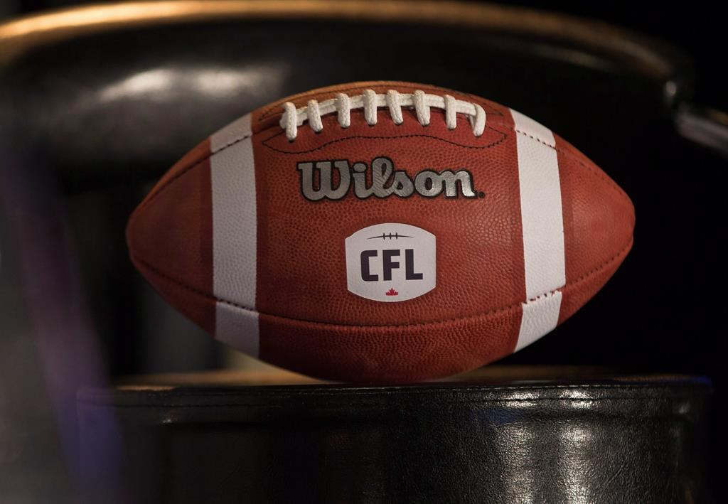 A football with the new CFL logo sits on a chair during a media conference in Winnipeg, Friday, November 27, 2015. The COVID-19 pandemic is creating twice as many challenges for some CFL players. THE CANADIAN PRESS/John Woods.