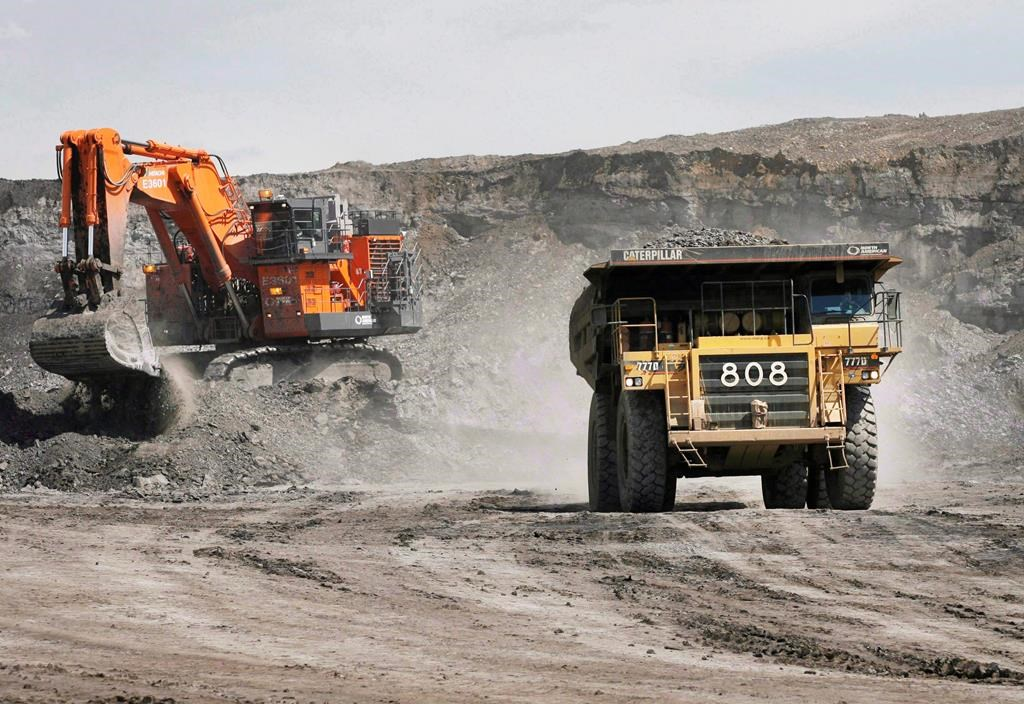 A haul truck carrying a full load drives away from a mining shovel at the Shell Albian Sands oilsands mine near Fort McMurray, Alta., Wednesday, July 9, 2008.
