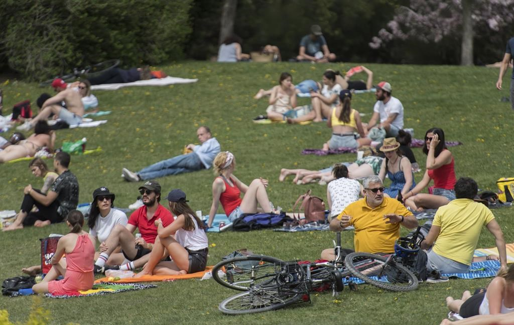 People enjoy a warm sunny day in a city park in Montreal, Sunday May 24, 2020.