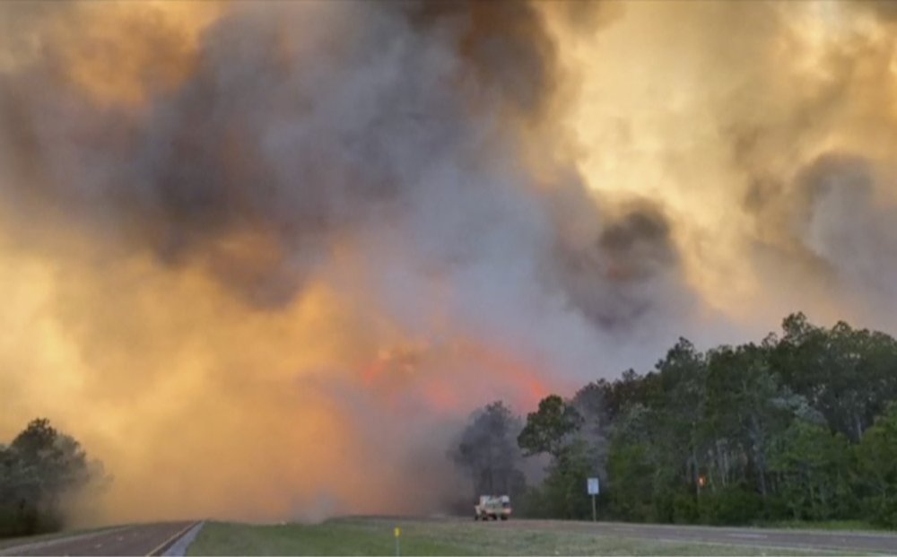 In this image made from video taken May 6, 2020 by the Florida Department of Agriculture and Consumer Services, fire and smoke rise from trees alongside a road in Santa Rosa County, Florida. Wildfires raging in the Florida Panhandle have forced nearly 500 people to evacuate from their homes, authorities said. (Florida Department of Agriculture and Consumer Services via AP) .