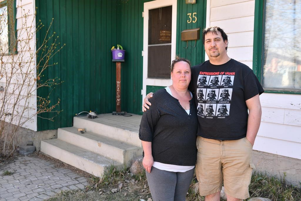 Homeowners Cora and Alec Dion pose by their home in Fort McMurray, Alta., on May 8, 2020. The Dions had about five feet of water in their basement as a result of recent flooding in downtown Fort McMurray. This marked the second time the couple faced evacuation from their home since the Horse River wild fire of May 3, 2016. THE CANADIAN PRESS/Greg Halinda.