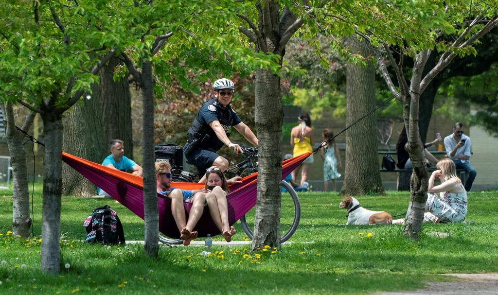 A bicycle police officer patrols Trinity Bellwoods Park in Toronto on Sunday, May 24, 2020. Warm weather and a reduction in COVID-19 restrictions has many looking to the outdoors for relief.