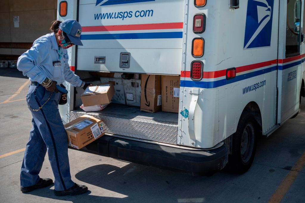 A United States Postal Service mail carrier finishes up loading her truck amid the coronavirus pandemic on April 30, 2020, in El Paso, Texas.
