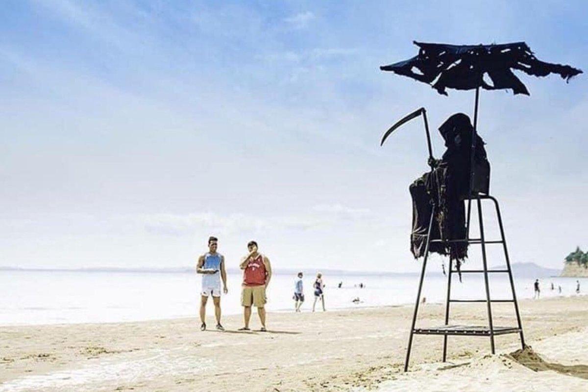 Daniel Uhlfelder is shown as the grim reaper on a beach in Florida.