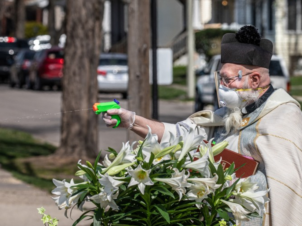 Rev. Tom Pelc of St. Ambrose Parish in Detroit, Mich., blessed churchgoers with a water gun full of holy water.