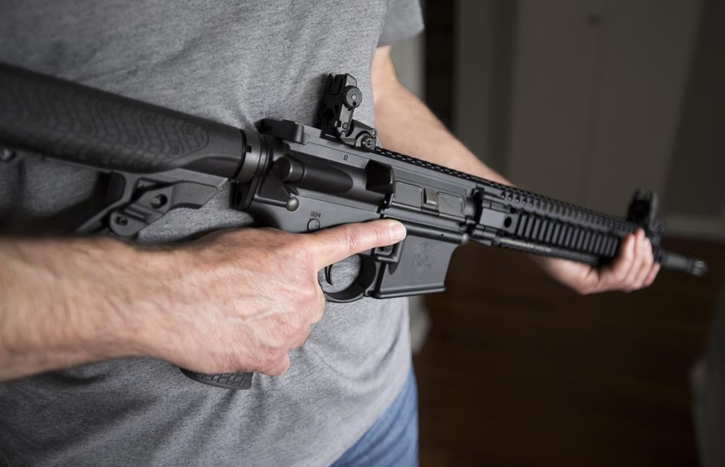 A restricted gun licence holder holds a AR-15 at his home in Langley, B.C. Friday, May 1, 2020.